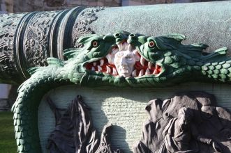 Two fierce dragons or wyrms on a huge green cannon outside the White Tower