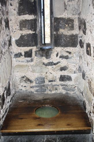 This is a thousand-year-old toilet. The smooth wooden seat was installed centuries later.