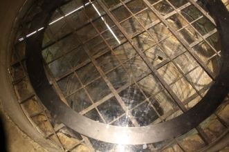 A well, blocked by an iron grid and glass