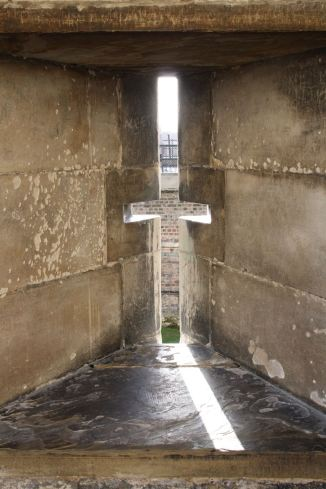 Cross-shaped slit in a stone wall at the Tower of London
